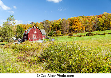 Hillside Barn - A large red barn at the bottom of a hill ...
