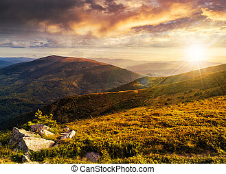 hillside with stones in high mountains at sunset - view on...