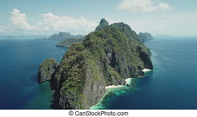 Hilly island at ocean gulf drone view. Green trees, plants at mountain rocks at paradise isle. Wonderful landscape of El Nido islet, Philippine, Visayas. Cinematic summer scenery aerial birds-eye shot