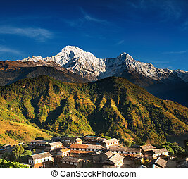 Landscape with village and mount Annapurna South, Nepal
