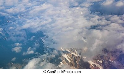 Himalayas high mountain range view in the window of an airliner at cruising altitude, peaks with snow
