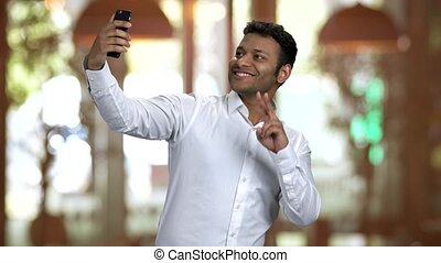Hindu businessman posing and taking selfie using his frontal camera. Restaurant indoors warm blurred background.