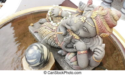 Hindu god the Ganesha statue in water tub