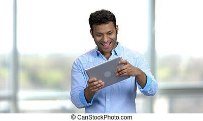 Hindu man playing games on tablet pc with facial expressions. Young hindu guy in a blue shirt excited with digital device standing in a bright room.