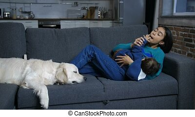 Hindu mom and infant relaxing on sofa with dog - Caring full...