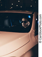 Hip asian man with sunglasses in car at night.