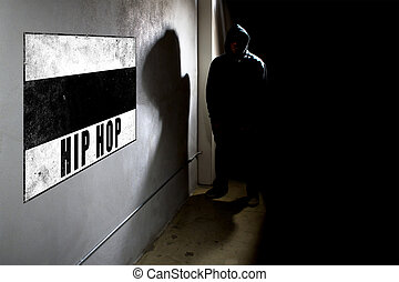 Hooded hip hop rapper next to wall graffiti with copy space
