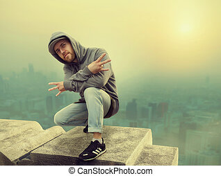 Hip hop performer posing, cityscape on background