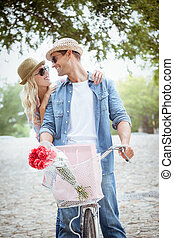 Hip young couple going for a bike ride on a sunny day in the...