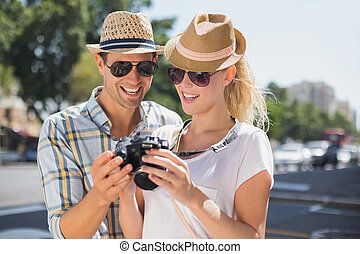 Hip young couple looking at their camera