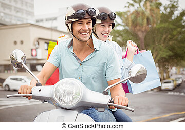 Hip young couple riding scooter with shopping bags on a...