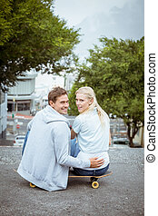 Hip young couple sitting on skateboard smiling at camera