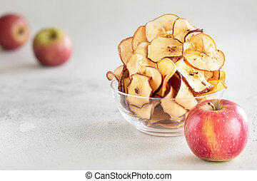 Hipped Dried apple chips in glass bowl with fresh apple in foreground on light background - Image