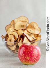 Hipped Dried apple chips in glass bowl with fresh apple in foreground on light background, vertical composition- Image
