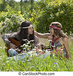 Hippie family playing guitar in the field
