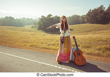 Hippie girl hitchhiking - Hippie girl with guitar ...