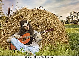 Hippie man playing guitar outdoors