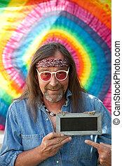 Hippie man pointing towards a blank blackboard