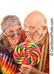 Hippie seniors licking a lollipop - Portrait of hippie...