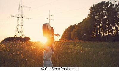 Hippie woman in golden field with acoustic guitar - asian...