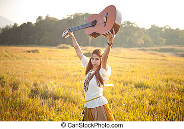 Hippie woman in golden field with acoustic guitar