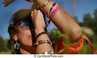 Hippie woman moves to the rhythm of music on a sunny day in the forest.