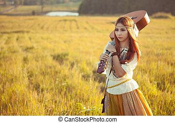 Hippie woman walking in golden field with acoustic guitar