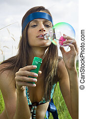 hippy blowing soap bubbles - beauty young woman blowing soap...