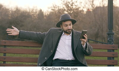 Hipser creative business man in hat using tablet computer for online video chat and sitting on city street bench in park during break