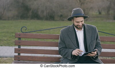 Hipser creative business man in hat using tablet pc computer and sitting on city street bench in park during break