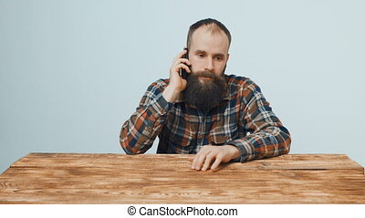 Hipster bearded man talking on mobile phone