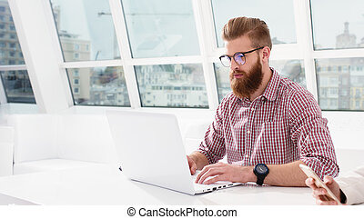Hipster businessman at the office works with a computer with his team