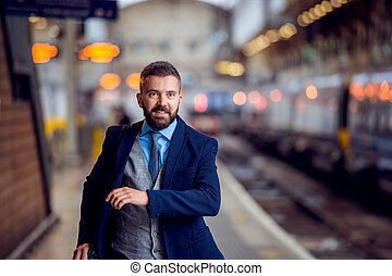 Hipster businessman at the staition running, catching the train