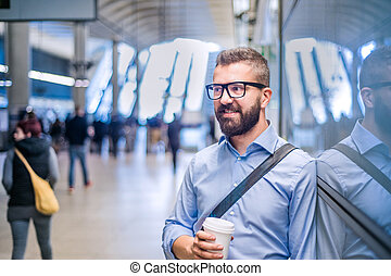 Hipster businessman holding a coffee cup, subway station