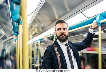 Hipster businessman inside the subway in the city, travelling to work.