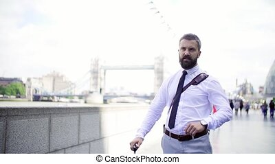 Hipster businessman standing by the river in London, a Tower...