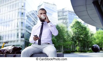 Hipster businessman with coffee and smartphone sitting on a bench on the street.