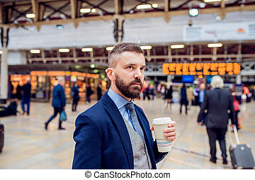 Hipster businessman with coffee cup at the train station