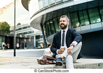 Hipster businessman with coffee sitting outdoors in the city.