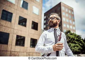 Hipster businessman with coffee standing on the street in London. Copy space.