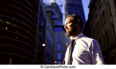 Hipster businessman with headphones standing on the street in London in the evening.