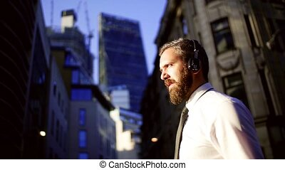 Hipster businessman with headphones walking on the street in London in the evening.