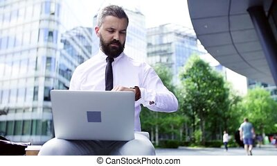 Hipster businessman with laptop sitting in the city,...