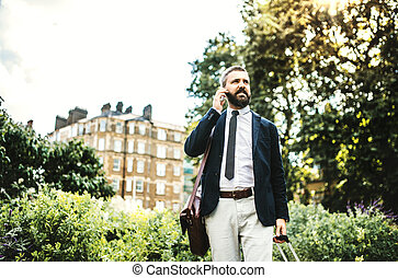 Hipster businessman with smartphone and suitcase walking in park in London.