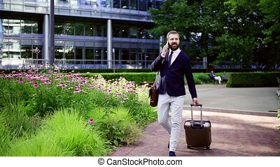 Hipster businessman with smartphone and suitcase walking in...