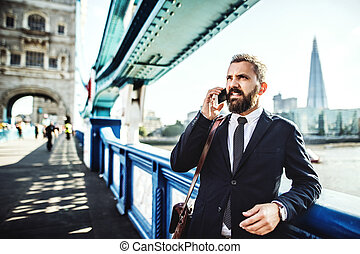 Hipster businessman with smartphone in the London city, making a phone call.