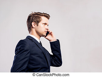 Hipster businessman with smartphone making phone call....