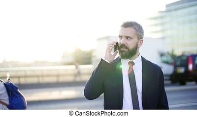 Hipster businessman with smartphone standing on the street...