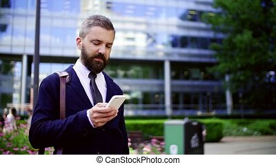 Hipster businessman with smartphone standing on the street in city, text messaging.