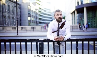 Hipster businessman with smartphone standing on the street in city, texting.